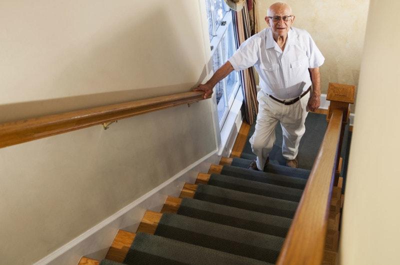 Photo of elderly man climbing stairs using handrail.