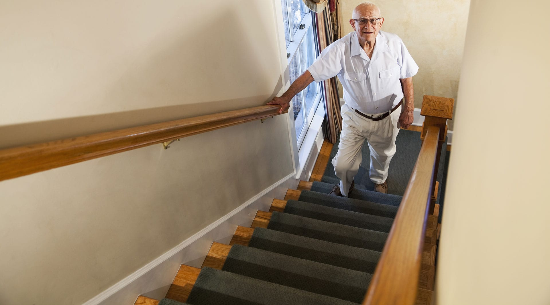 Photo of elderly man climbing stairs using handrail.