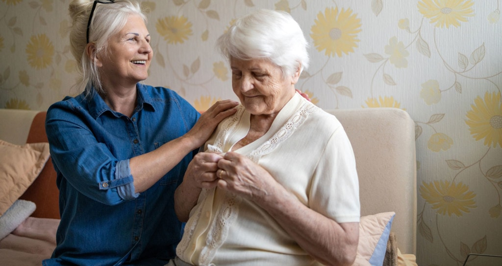 Photo of older woman helping elderly woman with dressing.