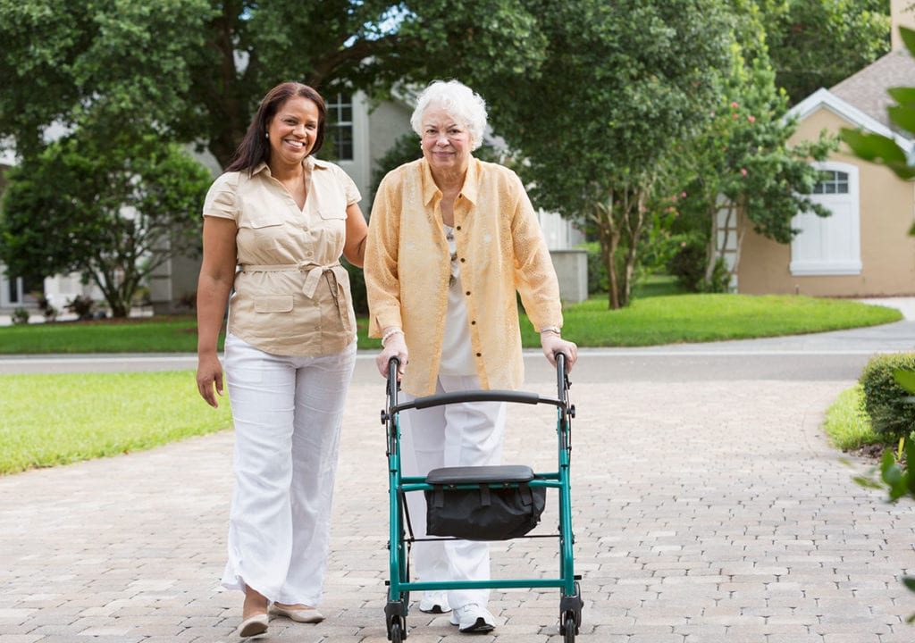 Photo of caretaker with elderly woman walking with a walker.