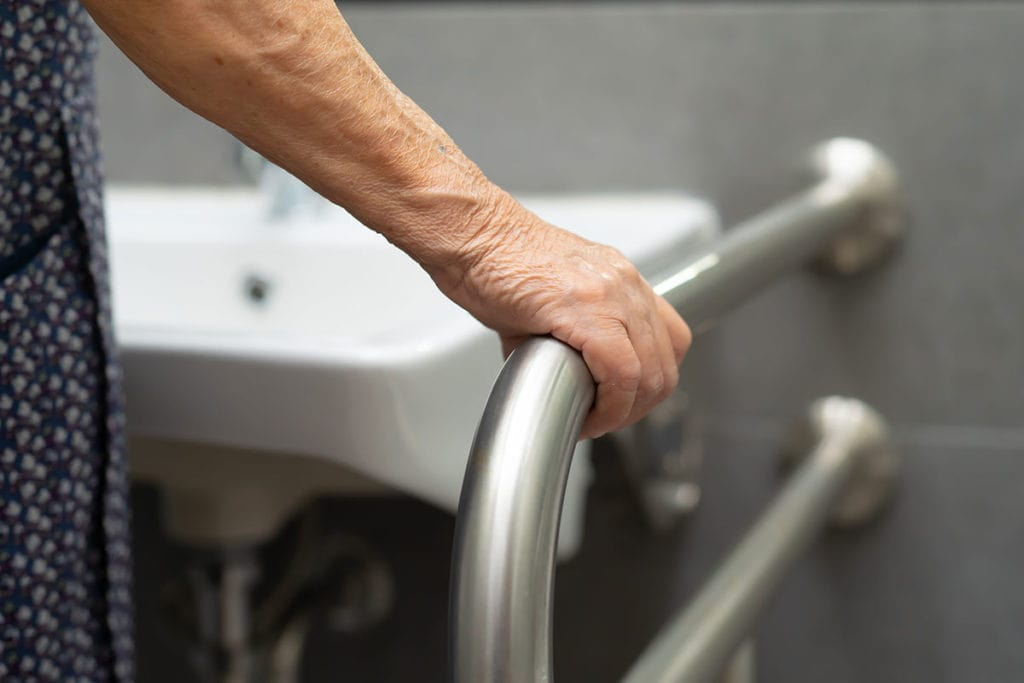 Photo of woman holding railing next to bathroom sink.