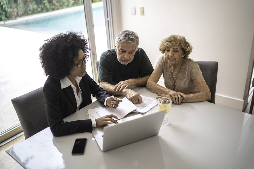 Photo of elderly couple looking at computer with younger woman with paperwork for estate planning.