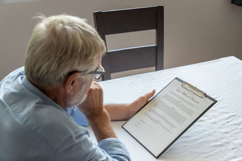 Photo of man looking at last will and testament.