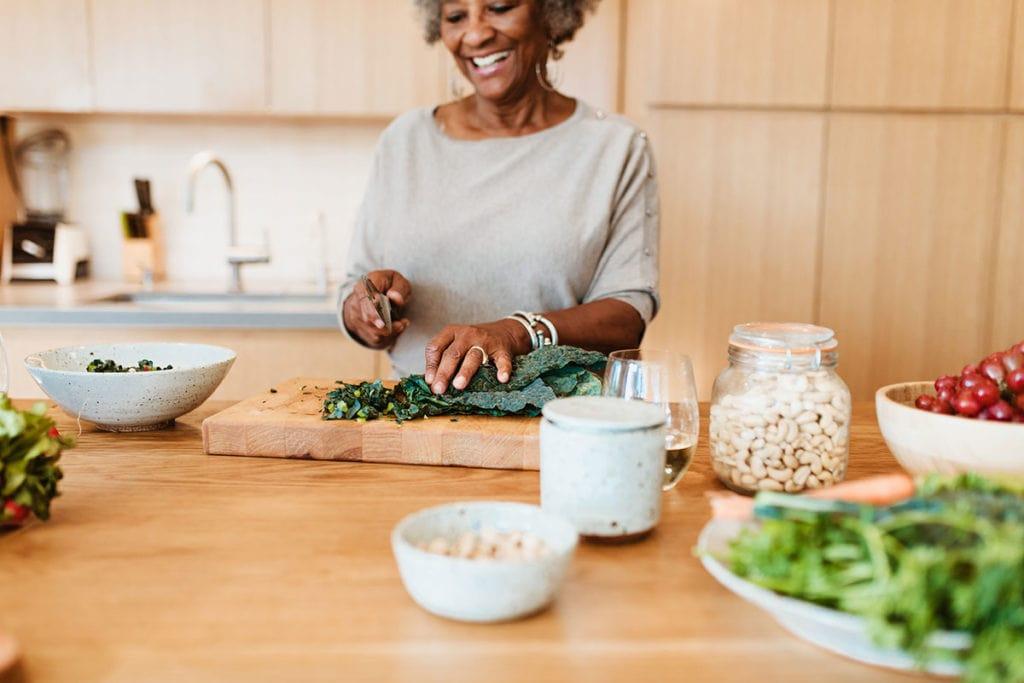 Photo of elderly black woman chopping kale.
