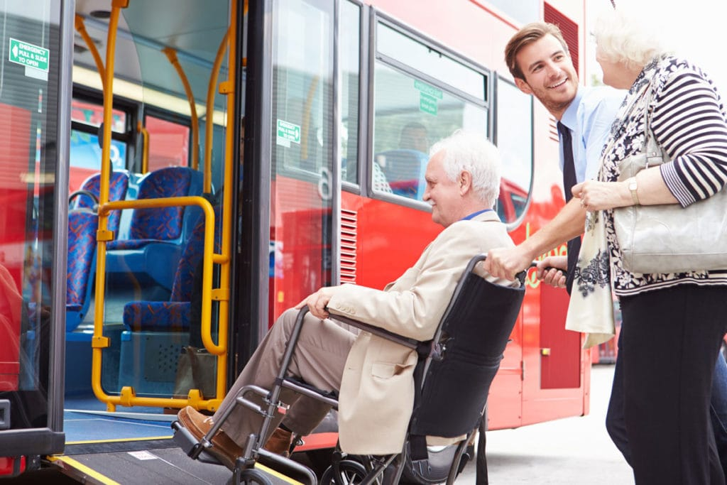 Photo of elderly man in wheelchair being wheeled onto bus.