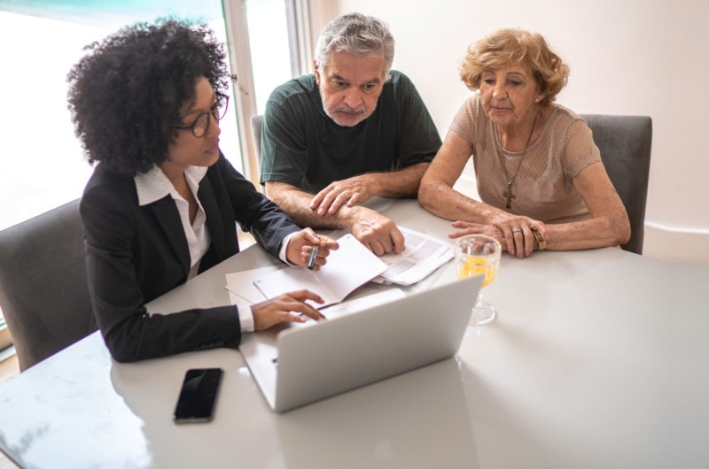 Photo of couple with financial planner at computer